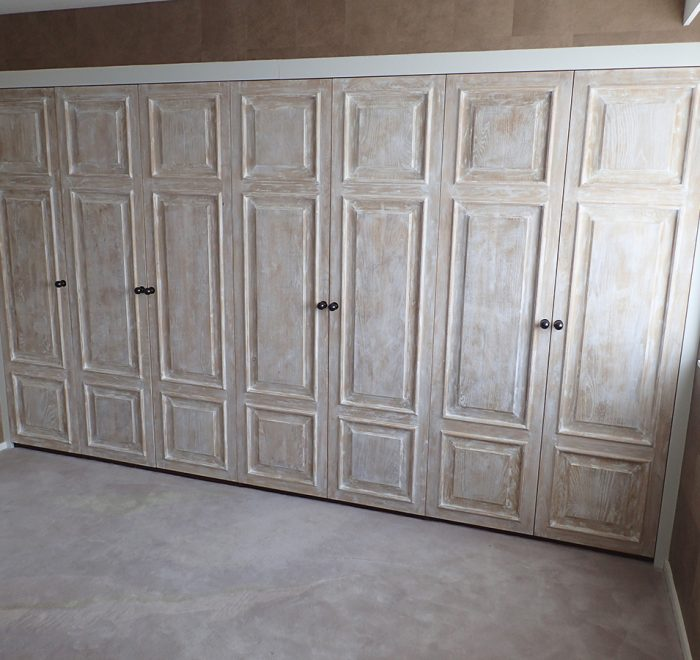 Distressed oak panelled wardrobe doors run